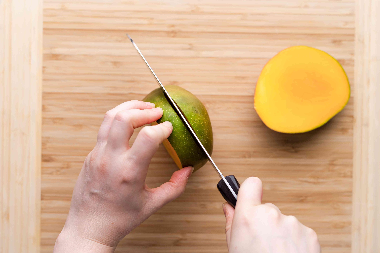 A person cutting a ripe mango.