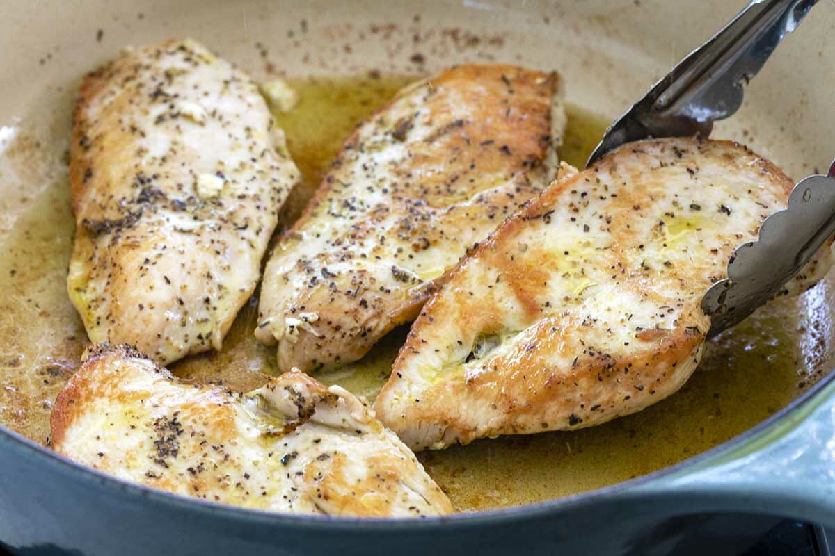 Best tuscan chicken pasta is being made by cooking the chicken breasts in oil in a dutch oven.