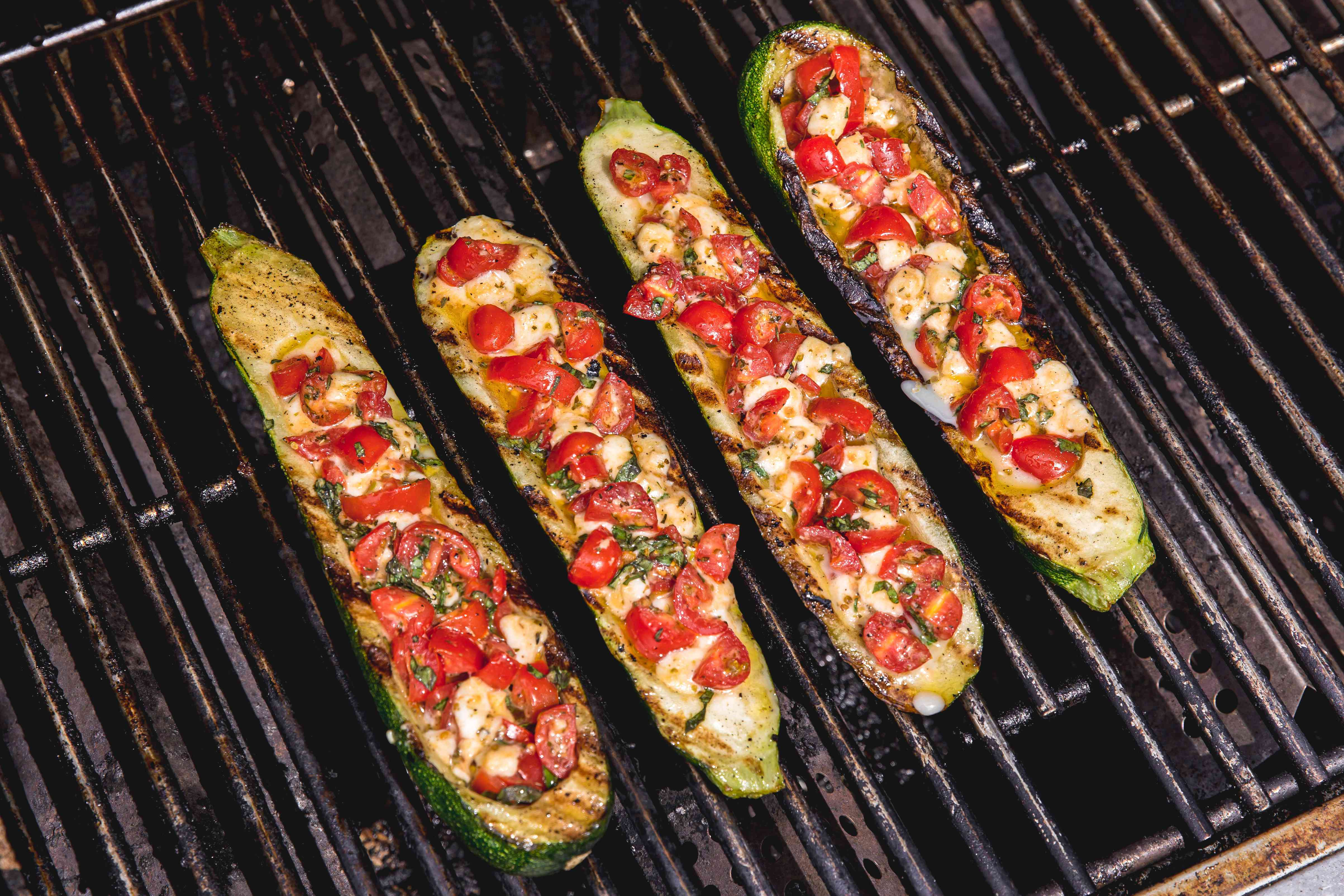 Grilling zucchini with tomatoes, mozzarella, and basil