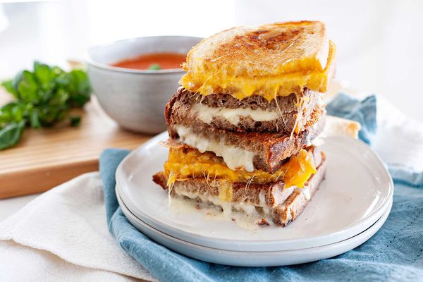 Grilled cheese sandwiches cut in half and stacked ontop of each other. Alternating with orange and white cheese with a bowl of tomato soup in the background.