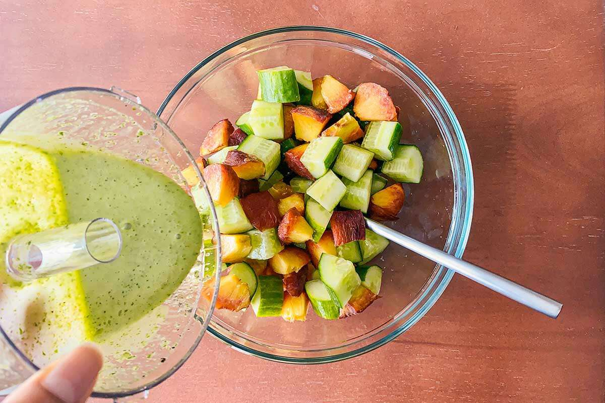 The bowl of a food processor with black pepper basil vinaigrette is being poured over a bowl of chopped cucumbers and peaches.