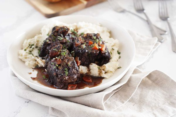 Mashed potatoes and short ribs on a plate.