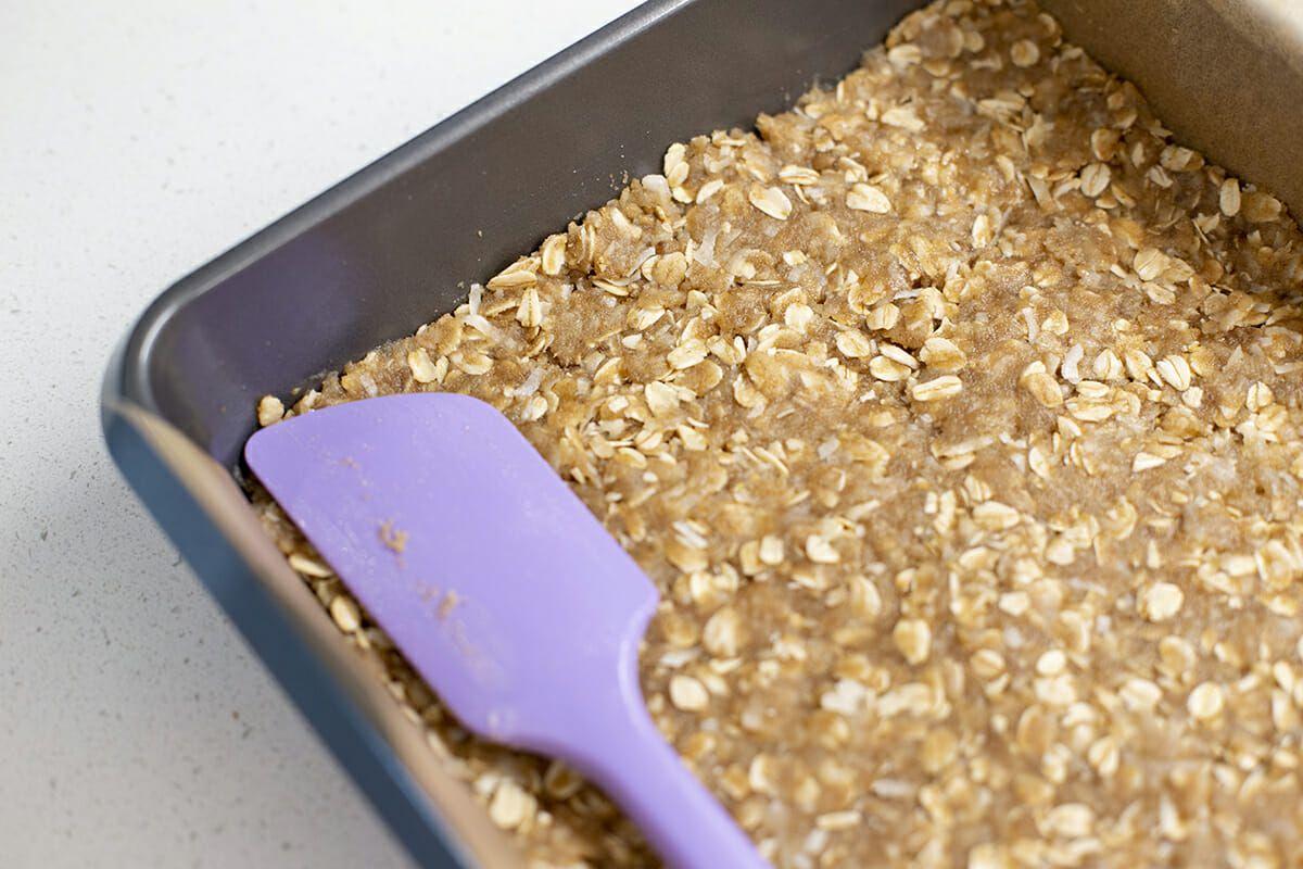 Caramel Chocolate Oatmeal Bars - purple spatula smoothing oatmeal