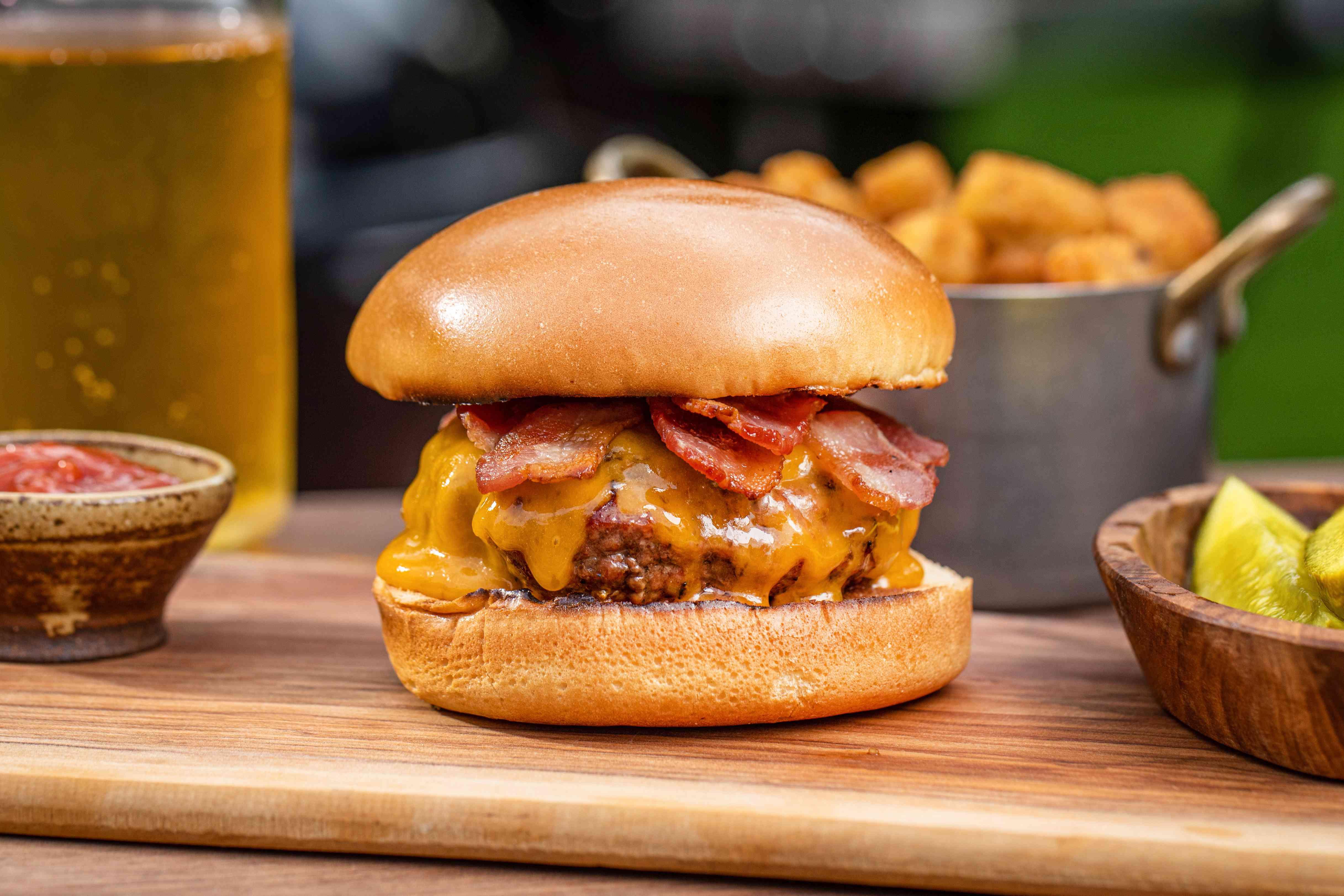 Best bacon cheeseburger set on a wood board outside.