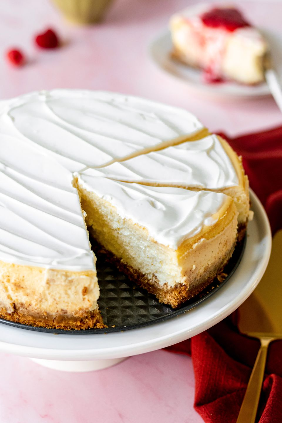 A cheesecake on a cake stand with a couple slices cut.