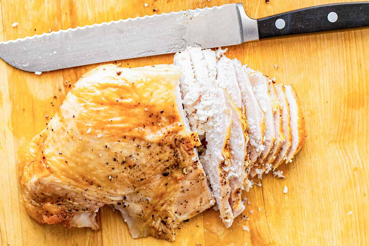 Roast turkey sliced on a cutting board and a knife for a turkey club sandwich.