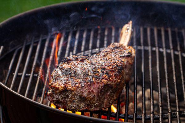 Seasoned bone in steak on a hot grill