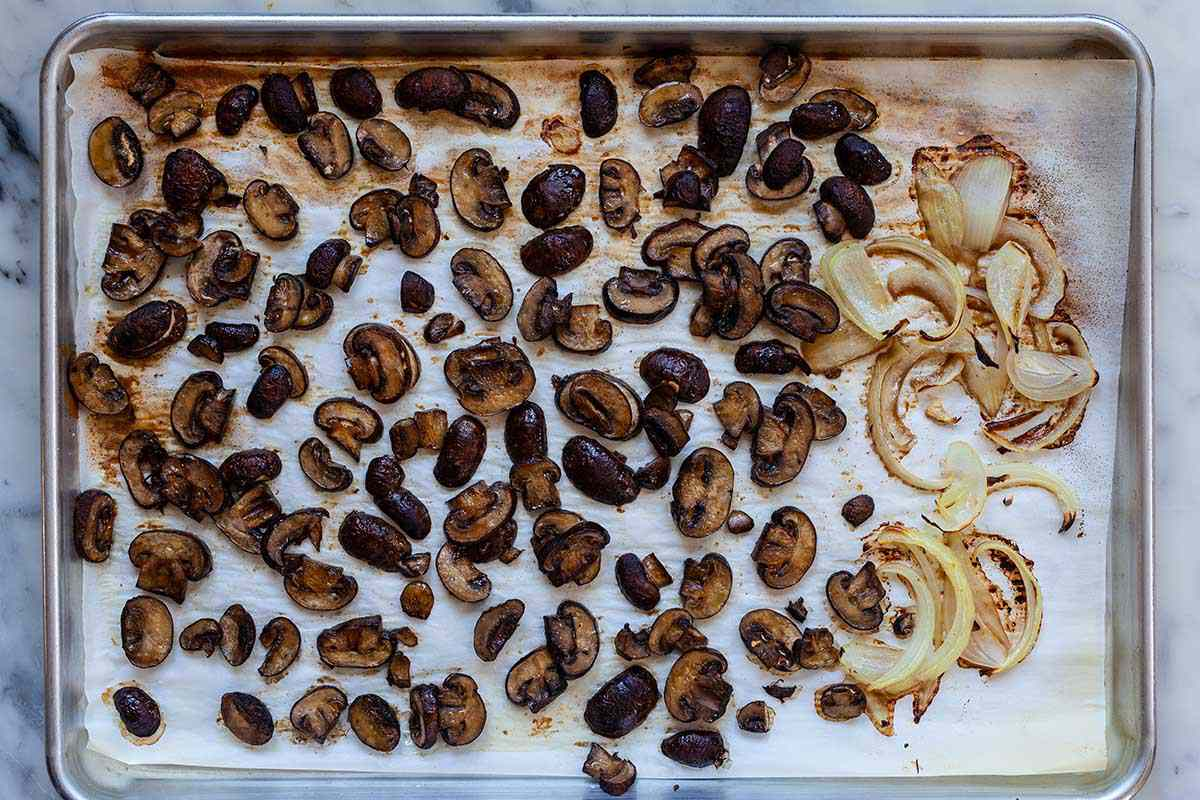 Roasted mushrooms and onions on a sheet pan for easy vegetarian gravy.