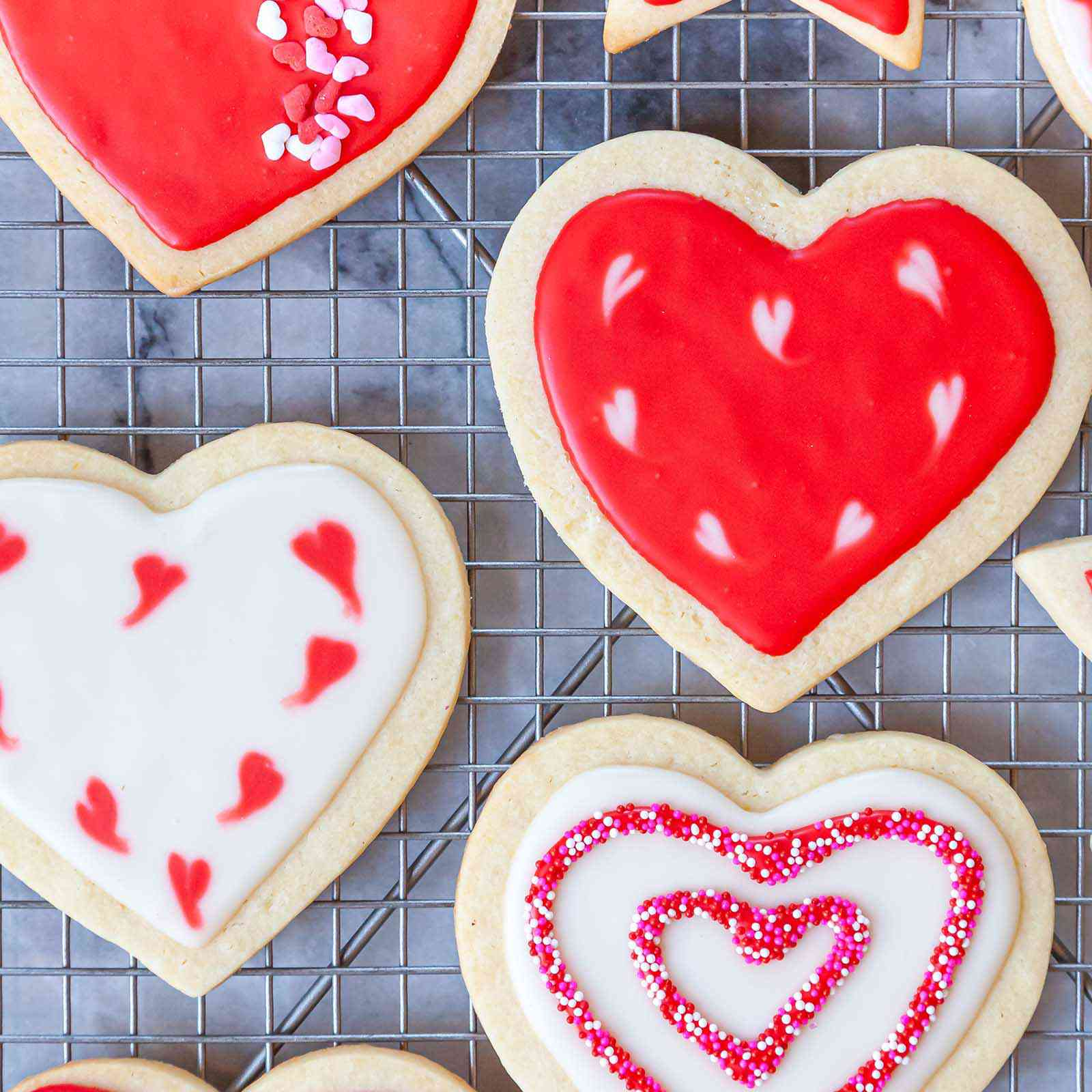 Easy Royal Icing Recipe piped into patterns on heart sugar cookies.
