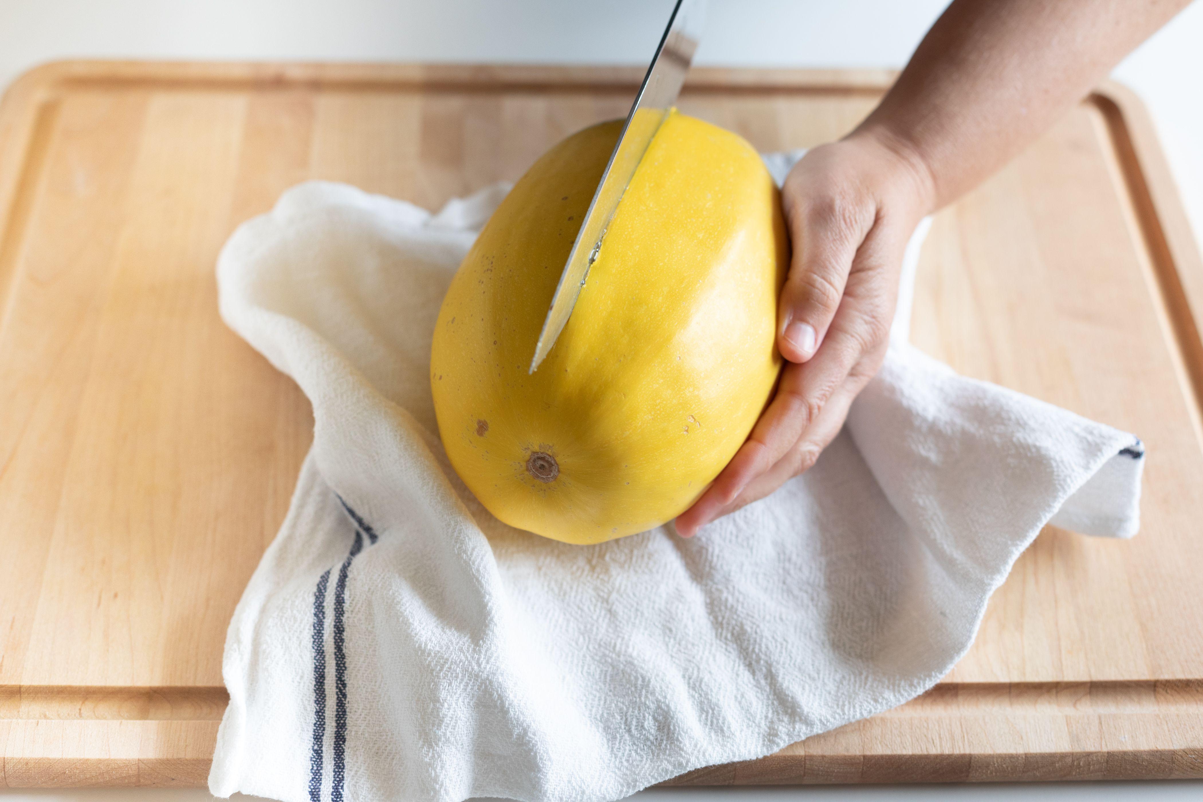 Cutting a spaghetti squash in half with a big chef's knife