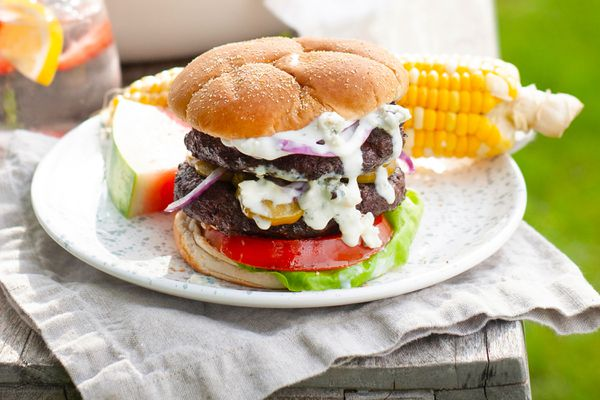 Burger dripping with blue cheese sauce, on plate with corn and watermelon