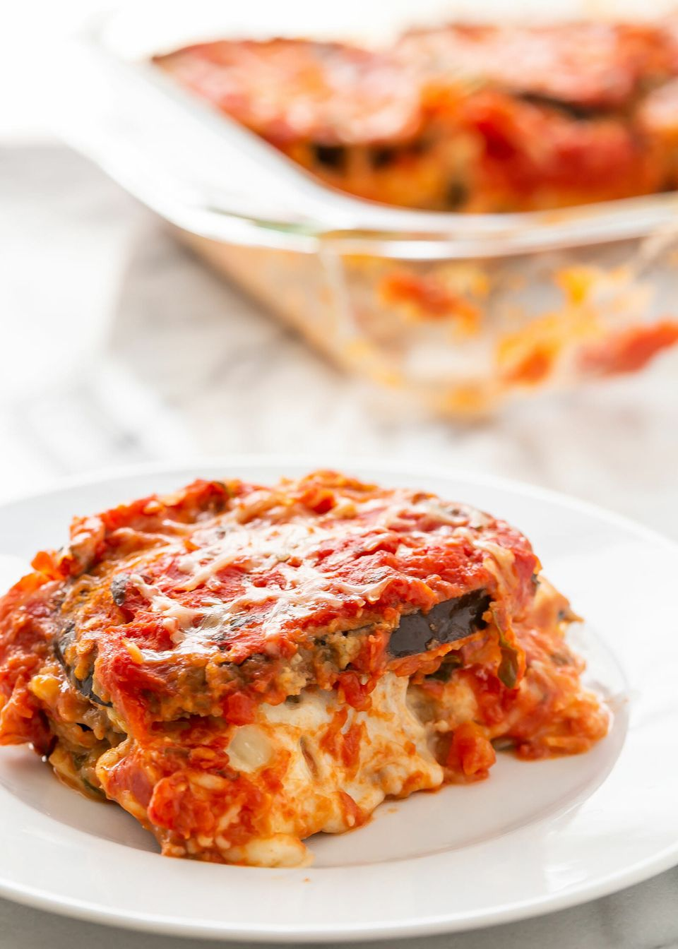 A slice of eggplant parmesan on a plate with the tray behind it.