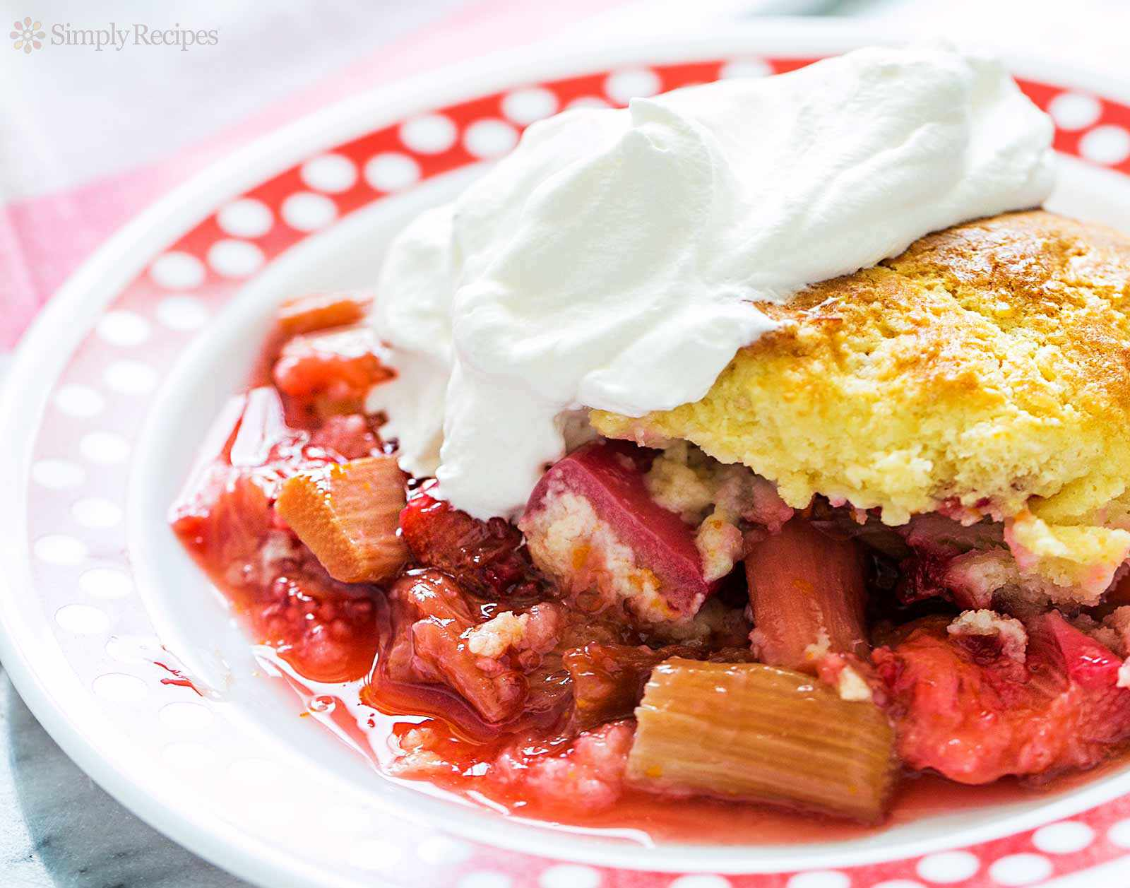 Strawberry Rhubarb Cobbler slice topped with whipped cream