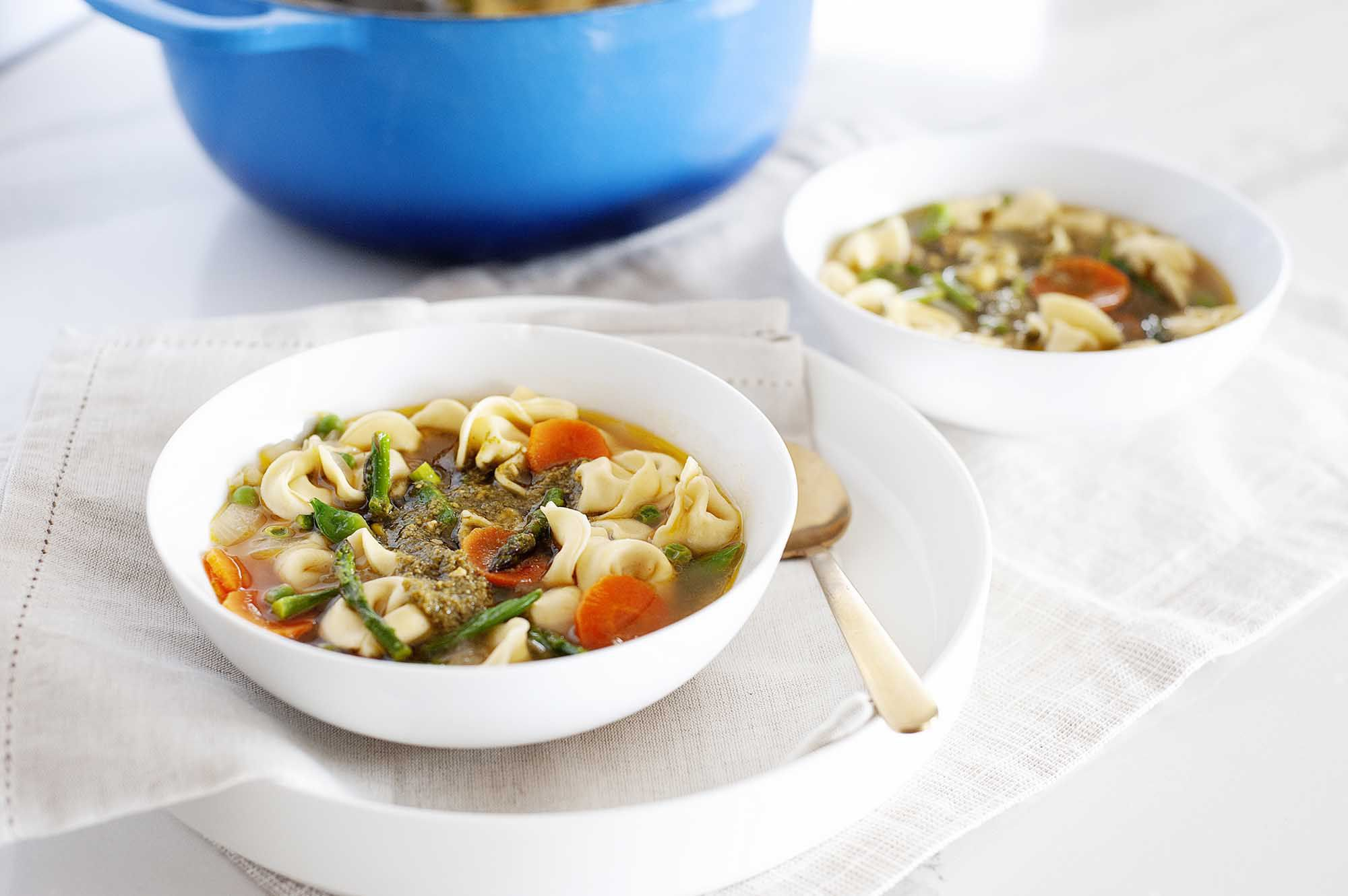 Pesto and tortellini soup with vegetables. A second bowl is to the right and a blue dutch oven is above.