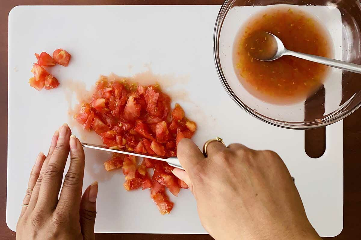 The core and seeds of a tomato are chopped on a cutting board to make easy baked stuffed tomatoes.