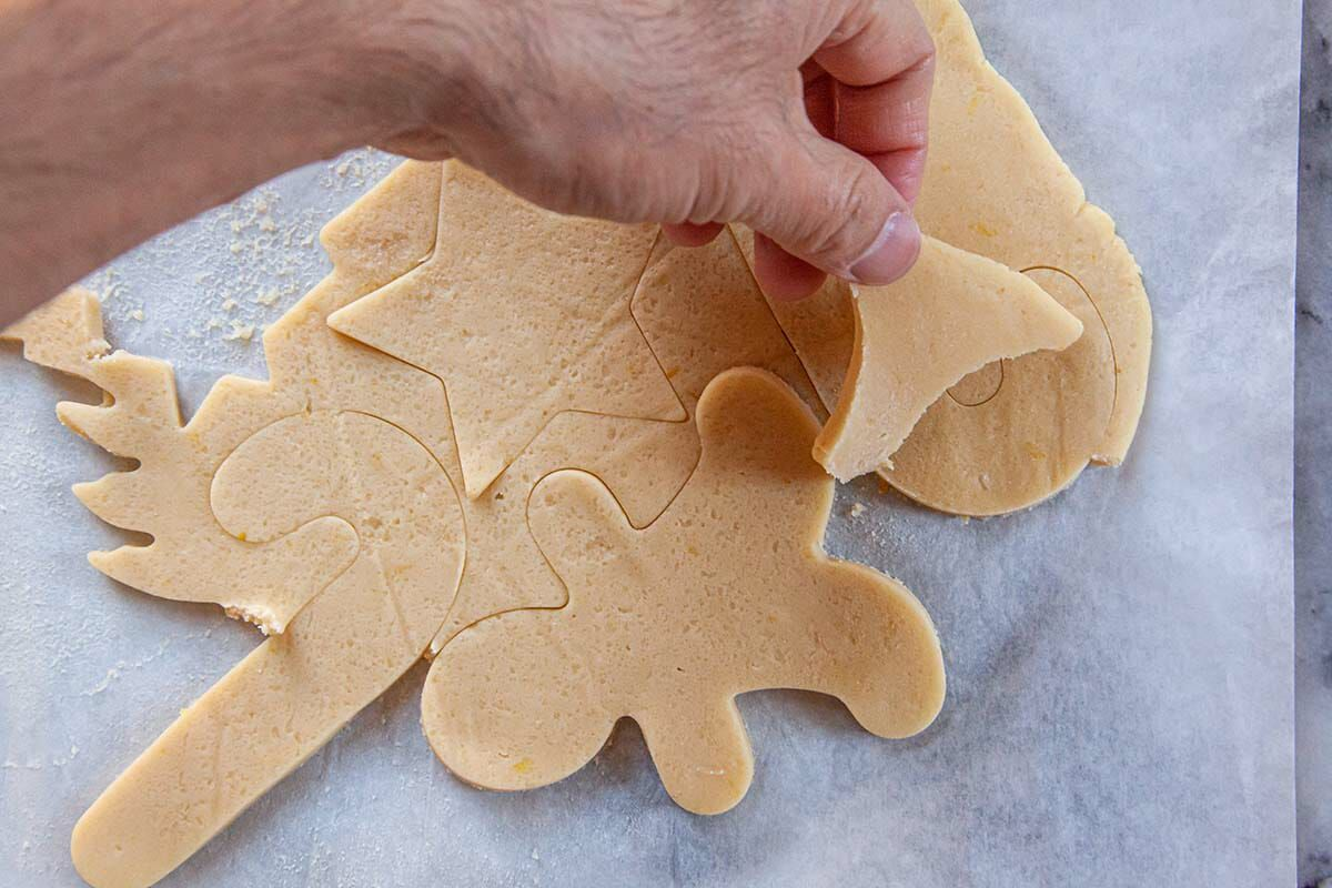 Removing excess dough from around the Cut Out Sugar Cookies before baking.