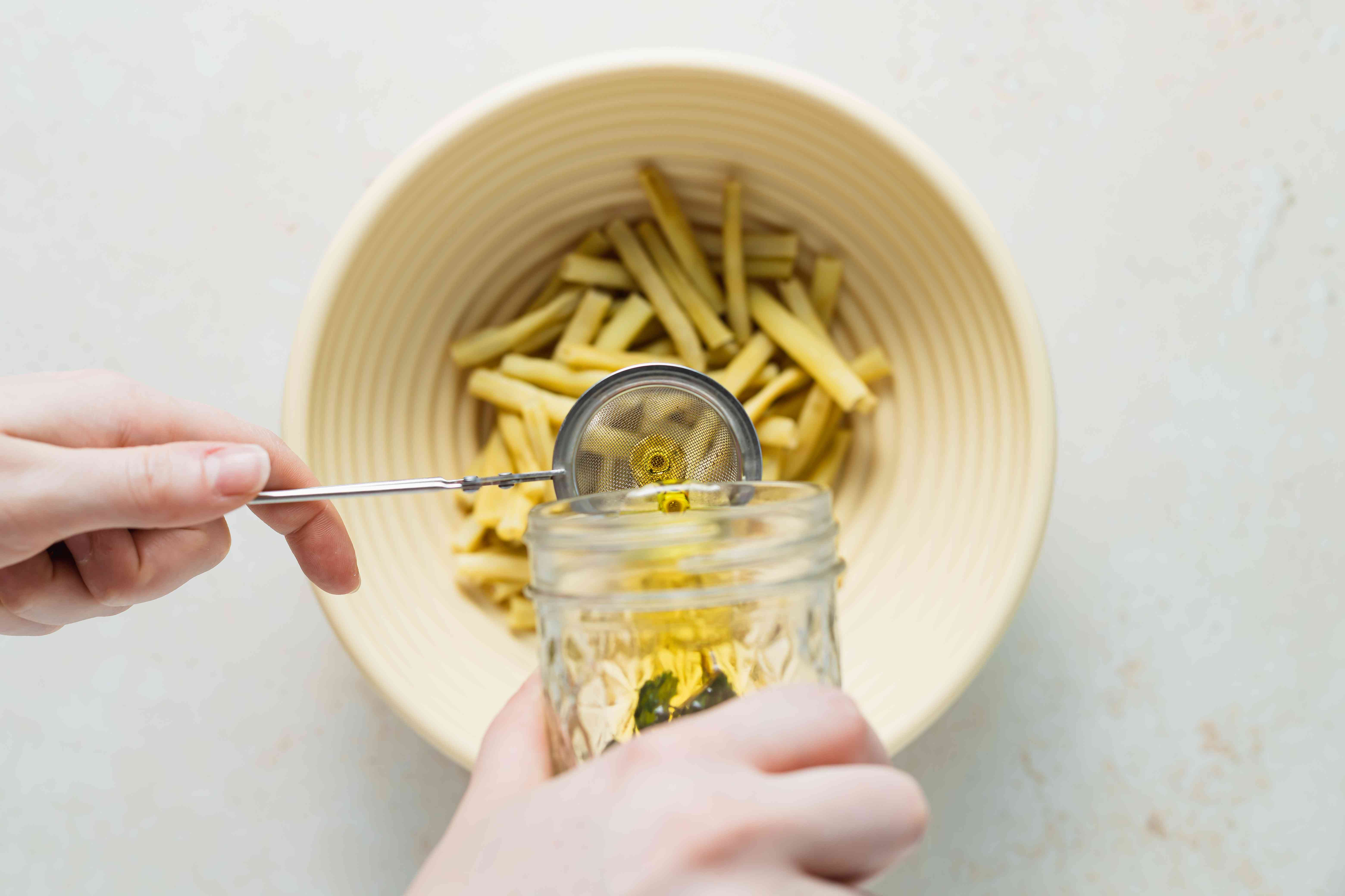 Adding dressing to a bowl of yellow beans.