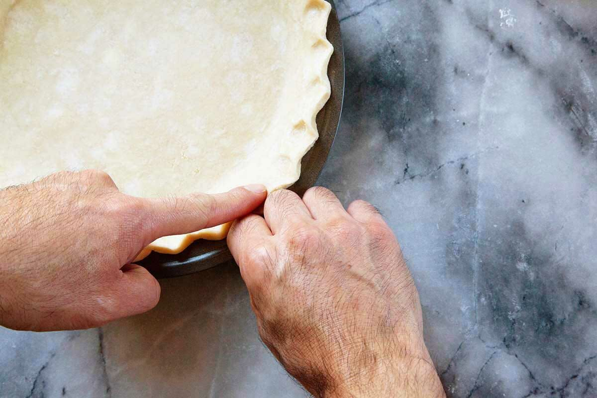 Pennsylvania dutch shoofly pie crust being crimped at the edges by two hands.