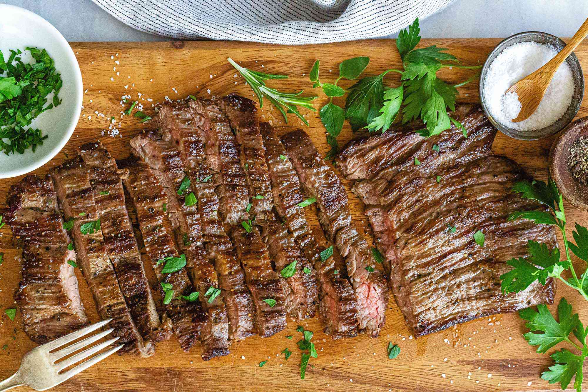 Sliced skirt steak on a wooden cutting board with herbs