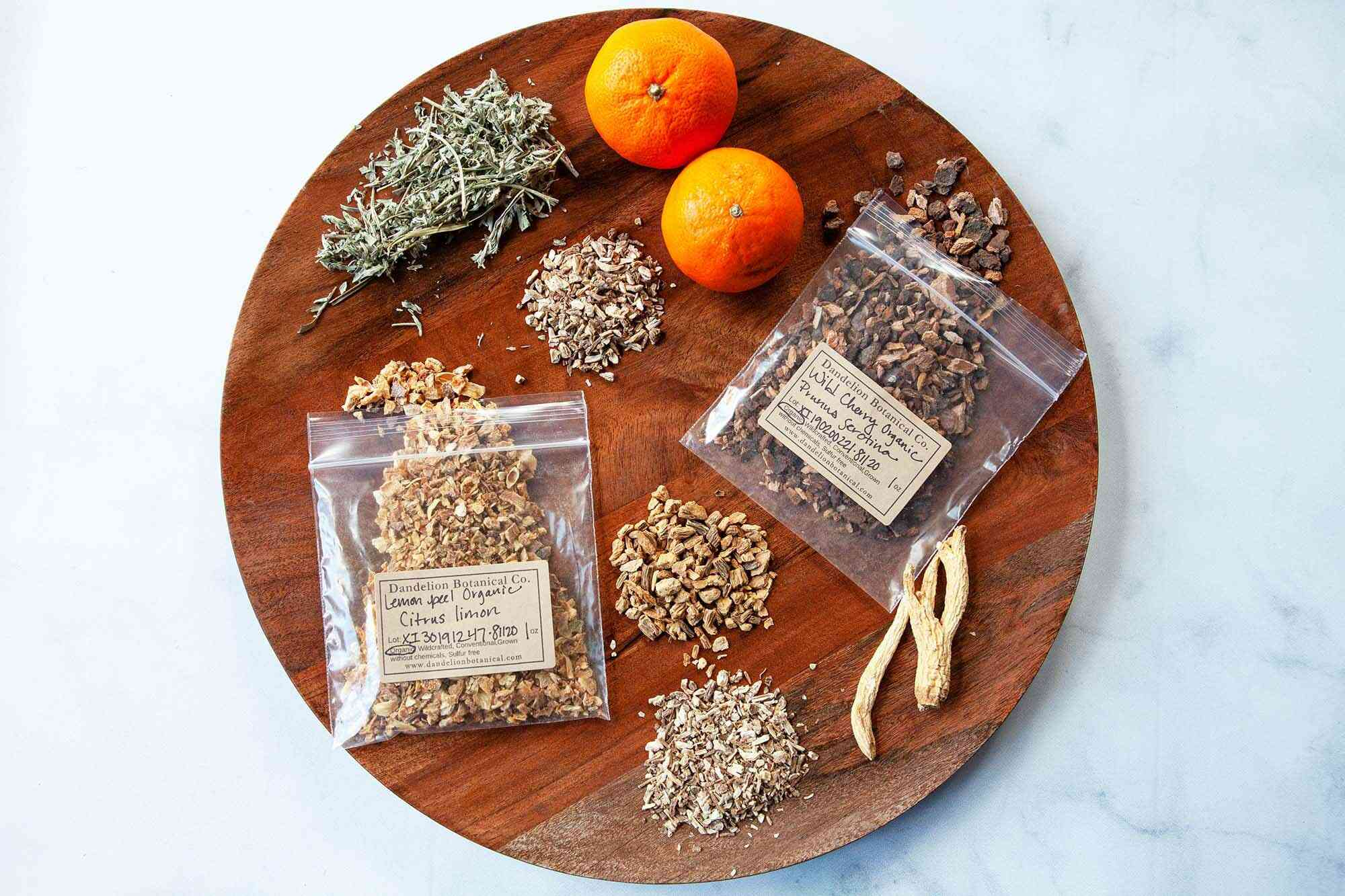A round tray with spices, herbs and oranges set around it to make Campari.