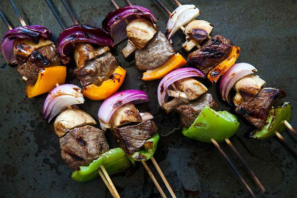 Shish Kabobs on wooden skewers with onions, bell peppers, and mushrooms, ready to eat