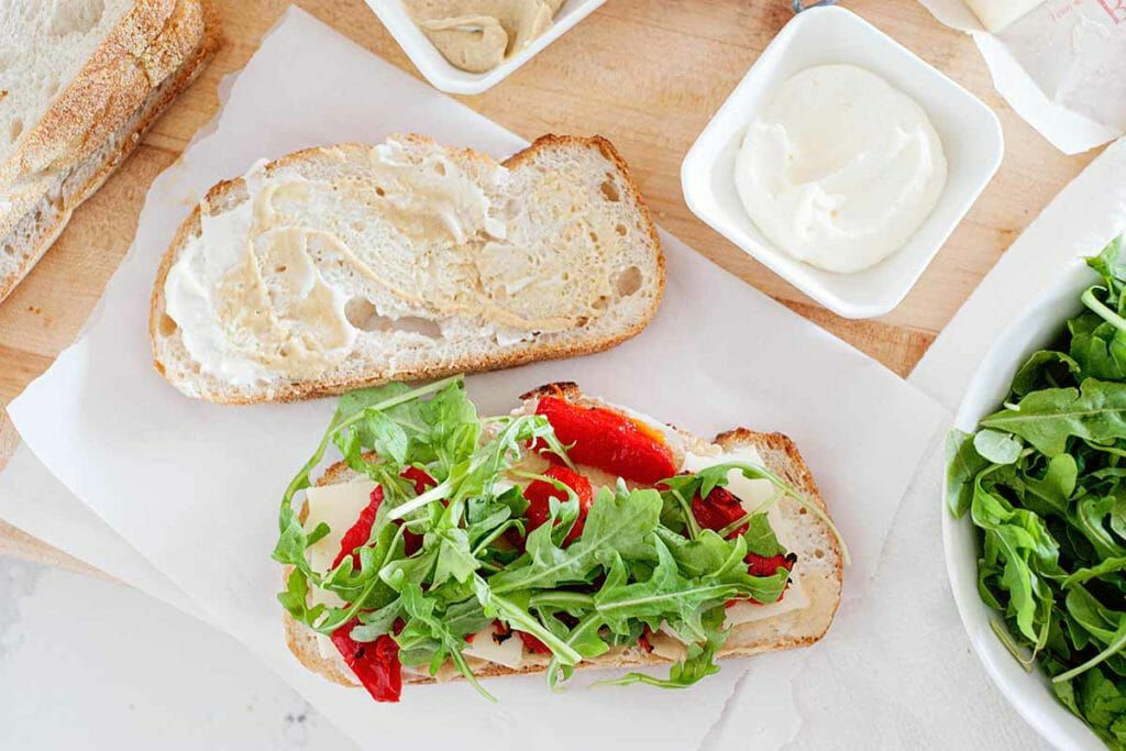 Layer the mozzarella, roasted red peppers, and arugula before making a Mozzarella Grilled Cheese Sandwich