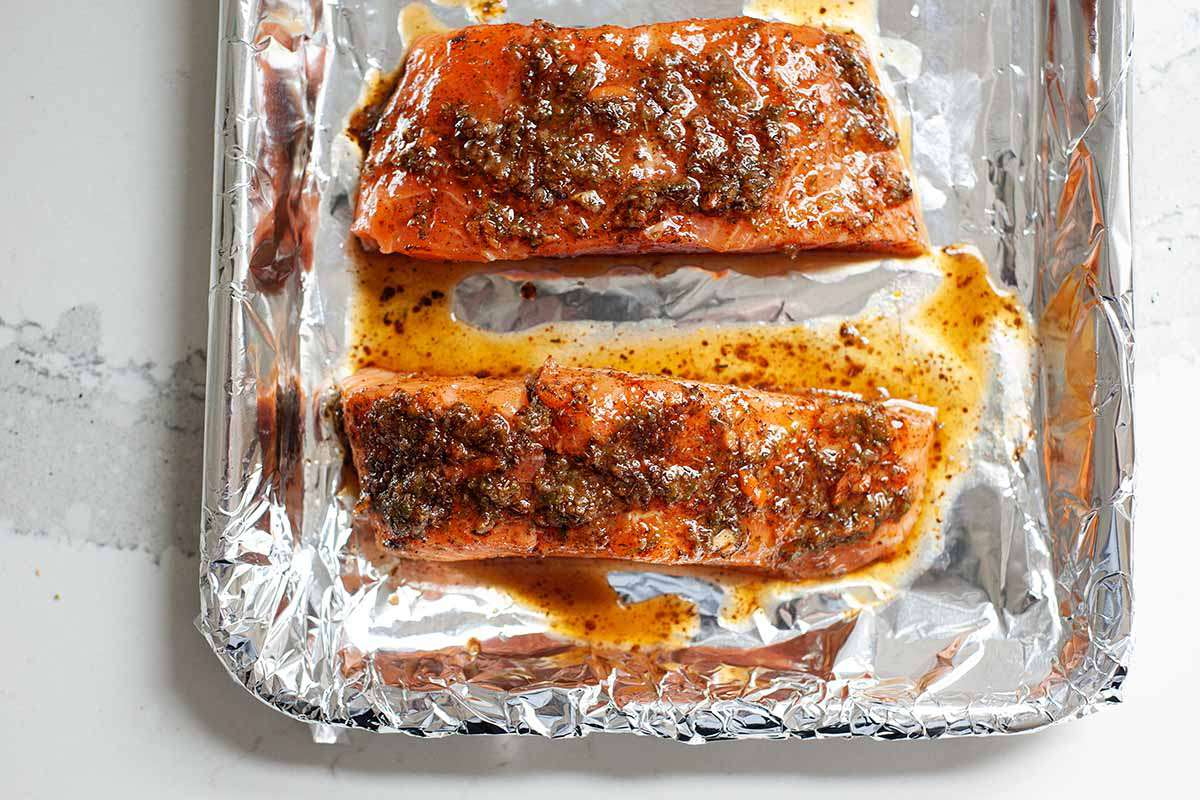 Two salmon fillets are on a foil-lined baking tray and coated with jerk seasoning. Some of the seasoning drips over the sides and on to the baking tray.