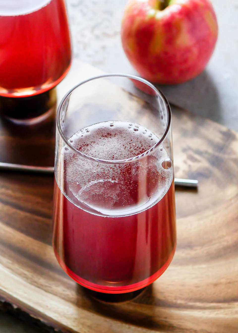 Close up of a Hard Cider and Pomegranate Mimosa on a wooden board with an apple, stir spoon and second glass behind it.