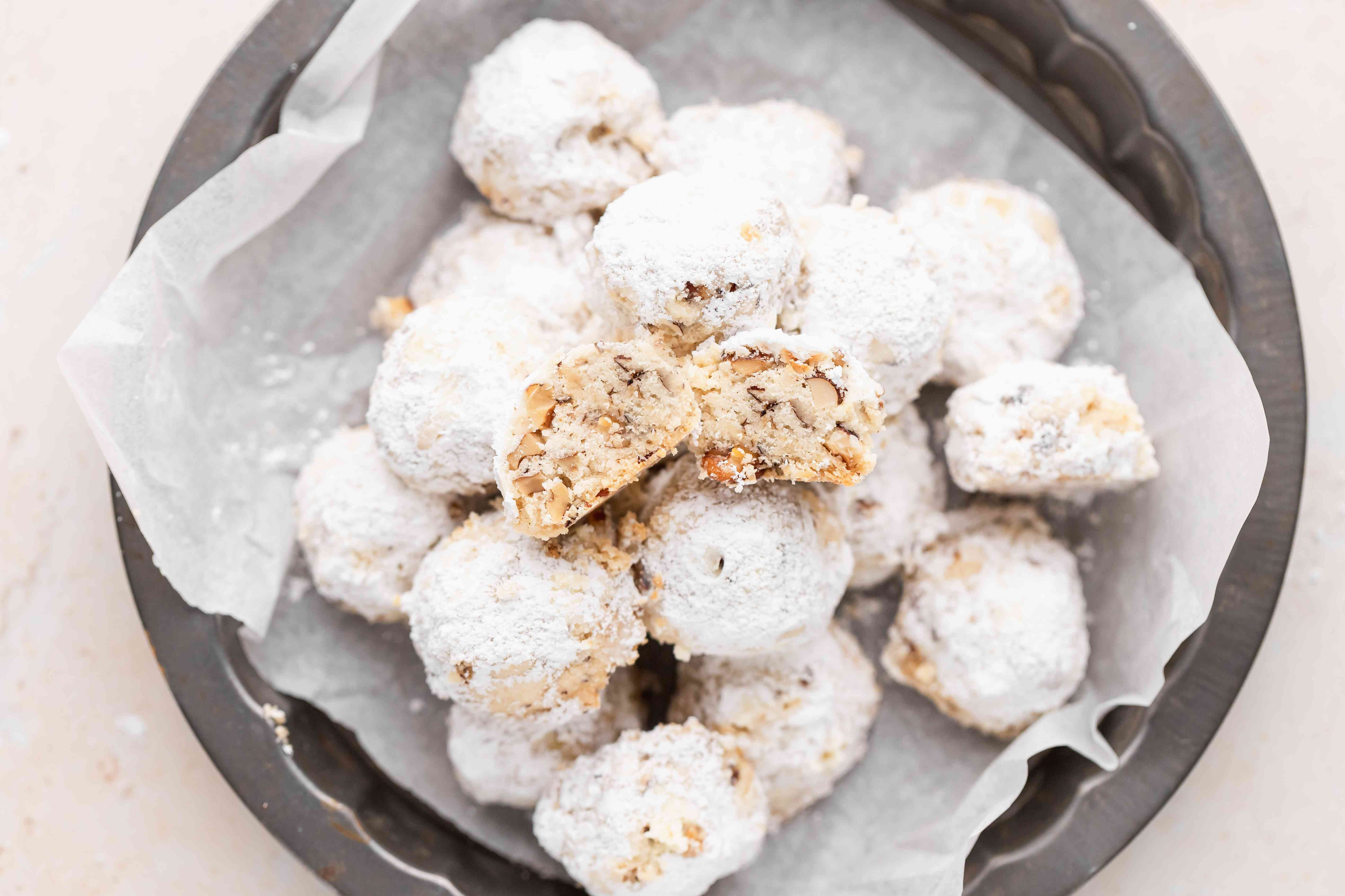 Overhead view of powdered sugar cookies piled on a plate with the top one cut in half to show the interior.