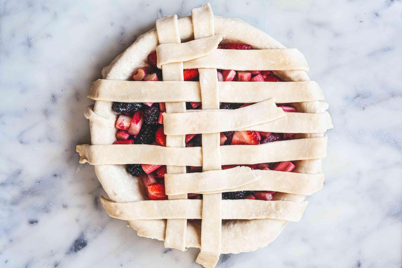 Weaving the strips of a lattice pie crust.