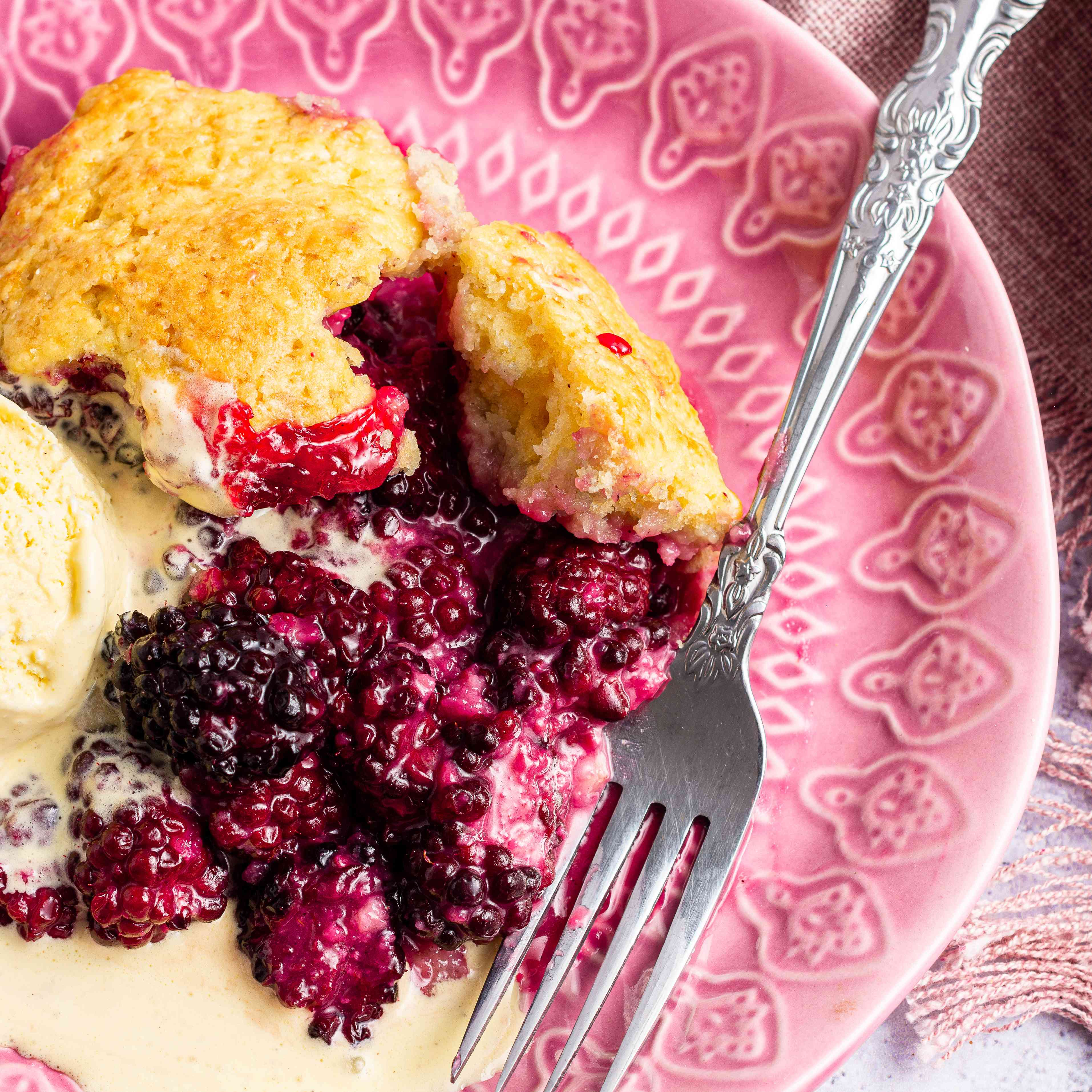 A plate with a piece of easy blackberry cobbler and a scoop of ice cream.