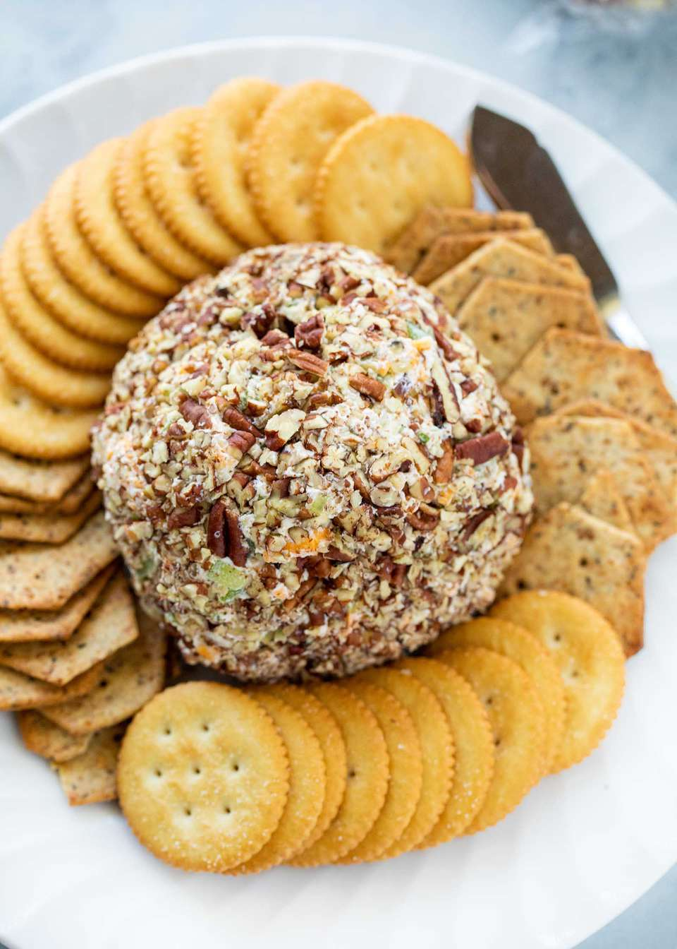 Classic cheeseball in the center of a platter and surrounded by crackers.