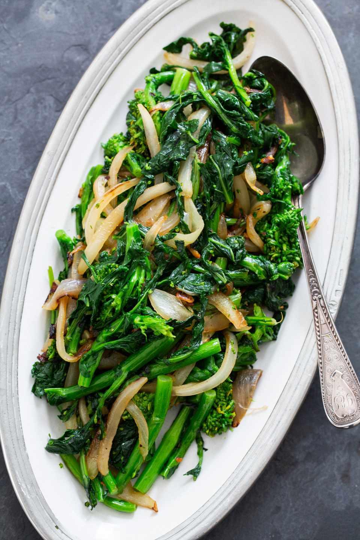Broccoli rob on a platter with sautéed onions.