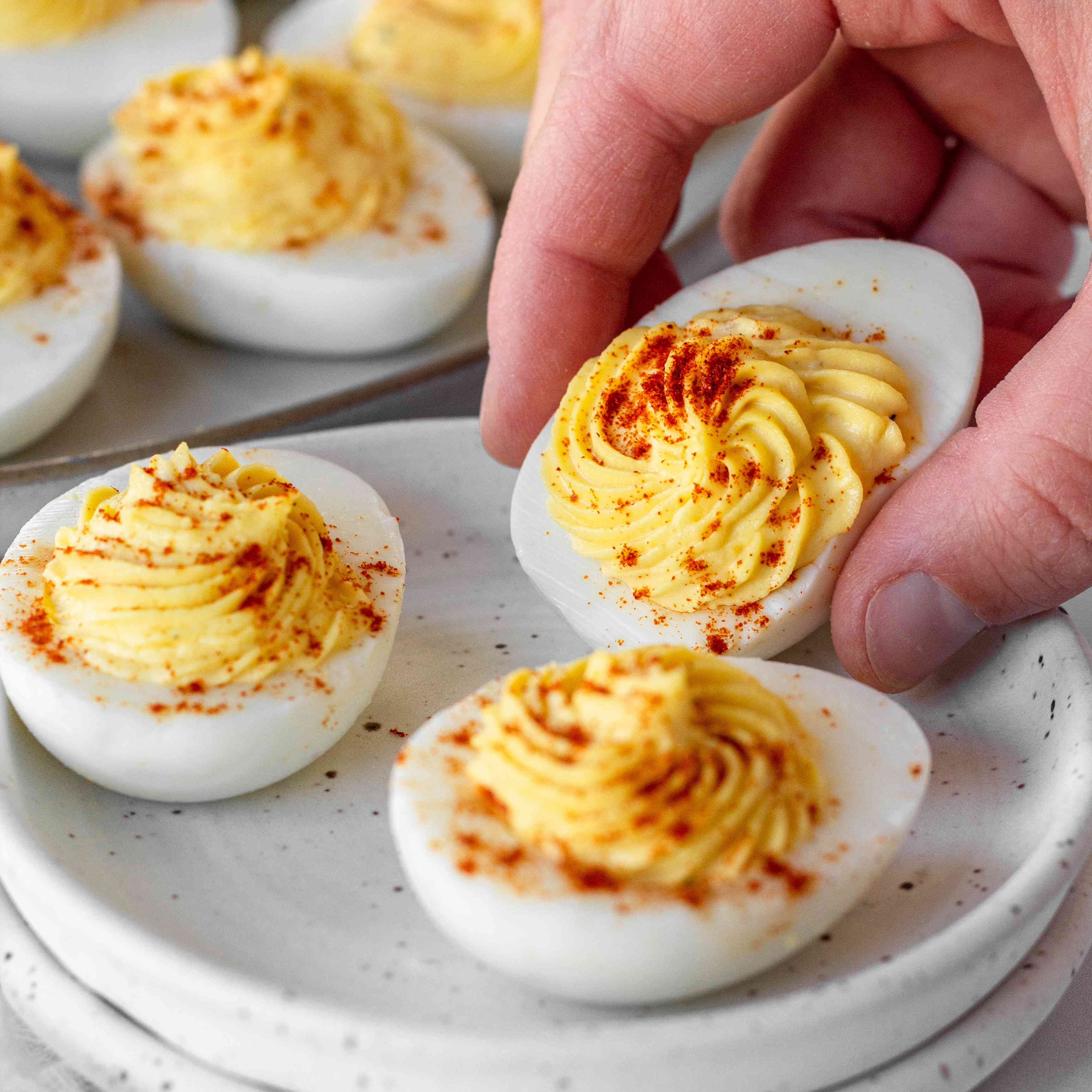 A hand picking up a Classic Deviled Egg off a small plate.