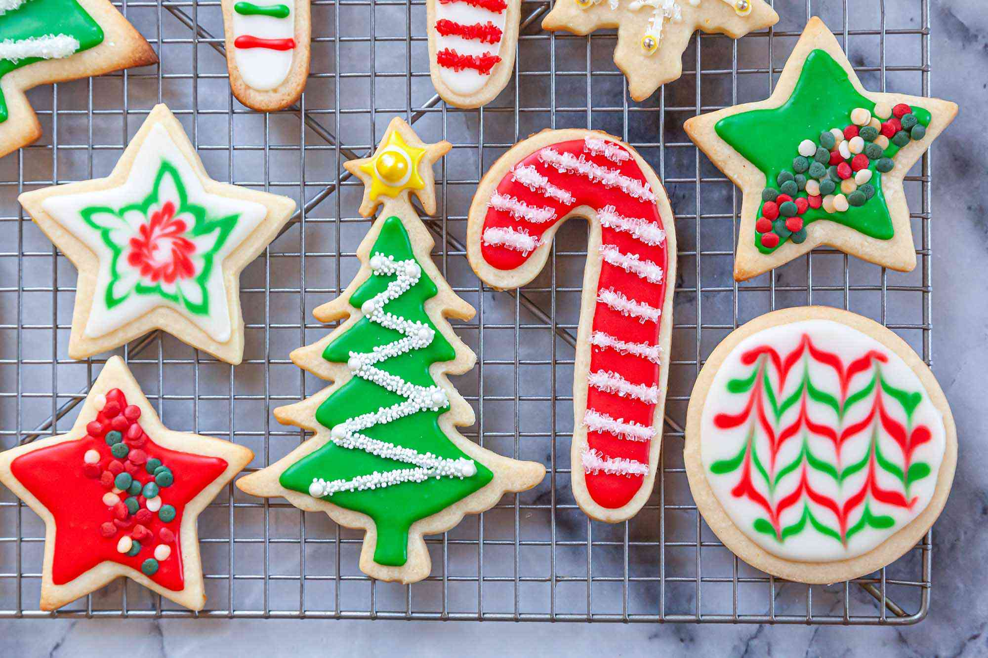 Cooling rack with festive cookies decorated with Royal icing and sprinkles.