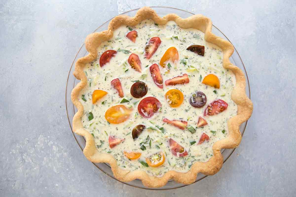 Zucchini and tomato quiche add the quiche filling, top with cut cherry tomatoes
