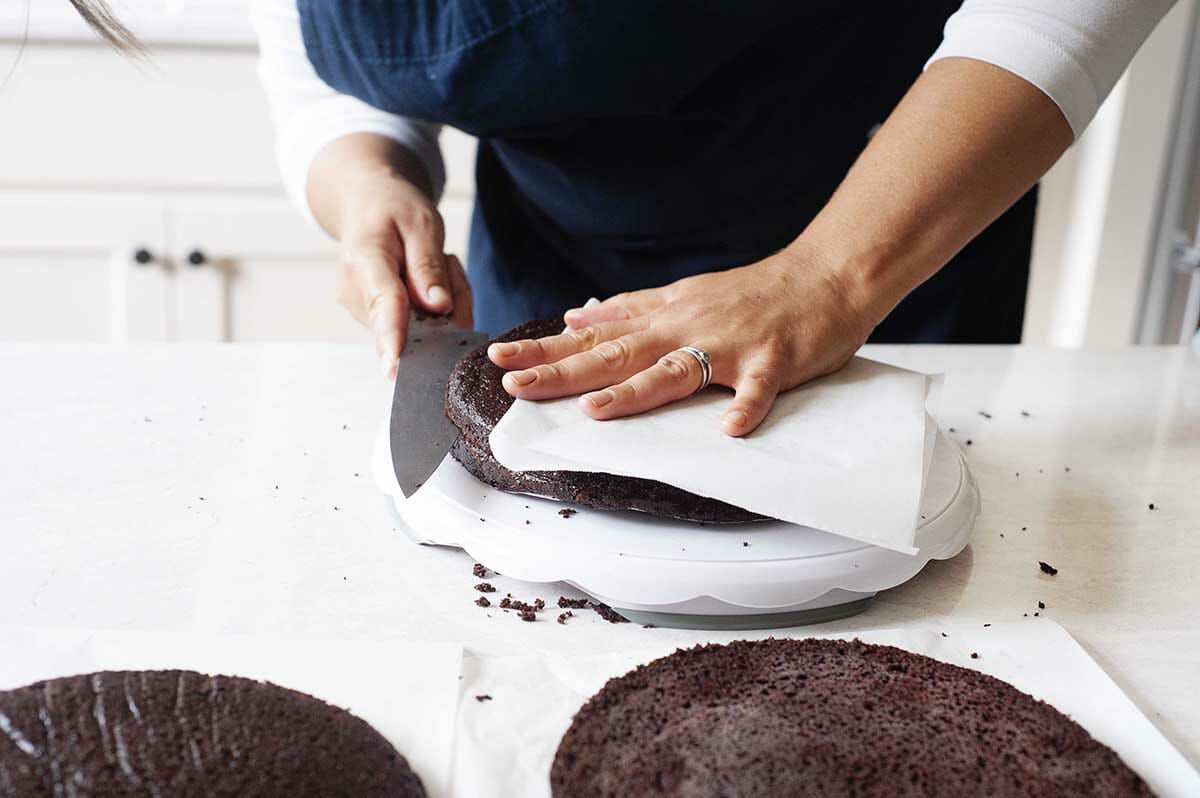 Chocolate cake rounds being cut horizontally to make Cherry Chocolate Cake with Whipped Cream.