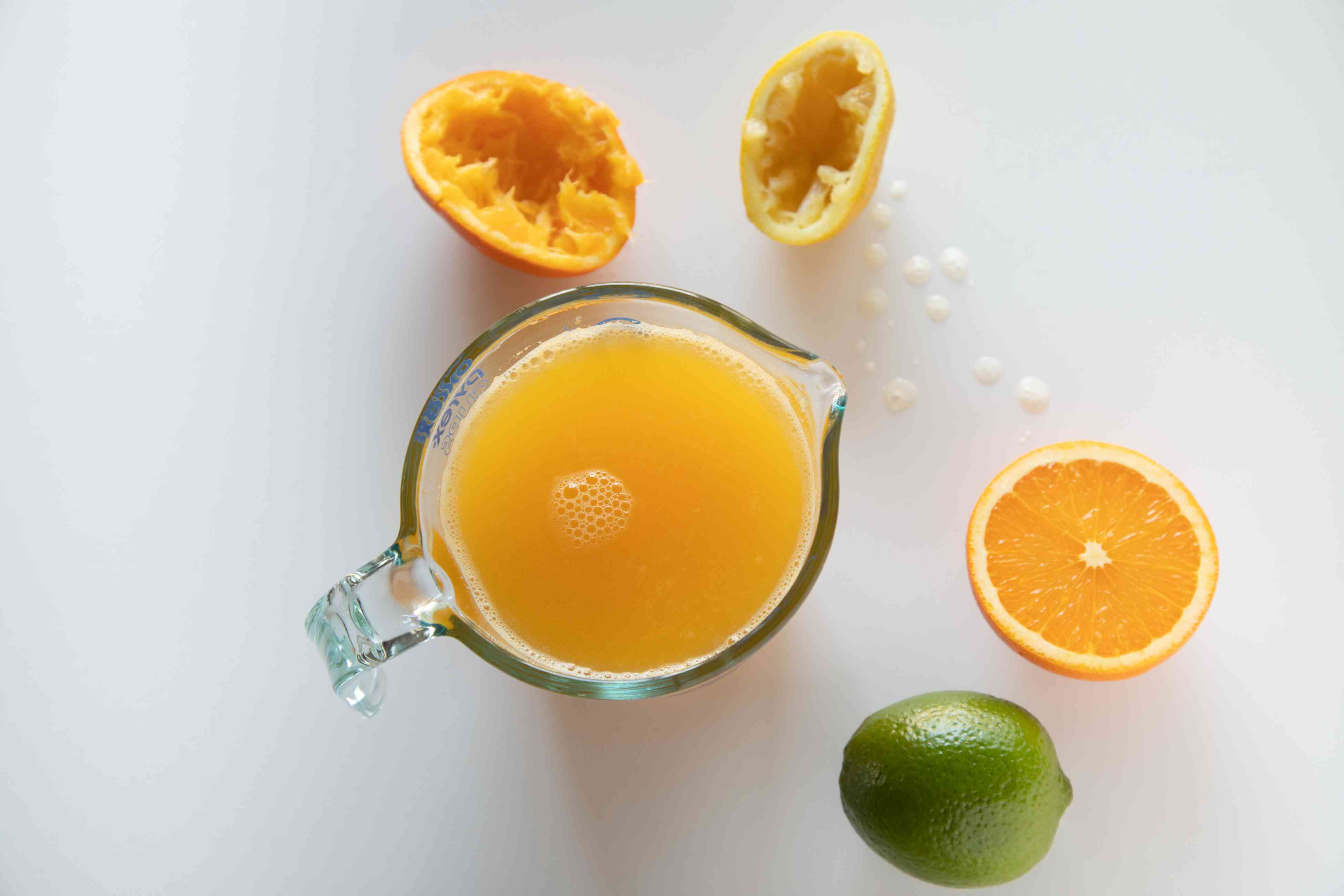 Fresh squeezed orange juice in a pitcher with oranges and a lime for a pork rib marinade.
