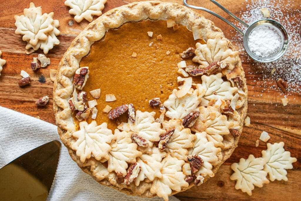 Decorating a pumpkin pie with leaves cut out of pie dough for Thanksgving family ideas.