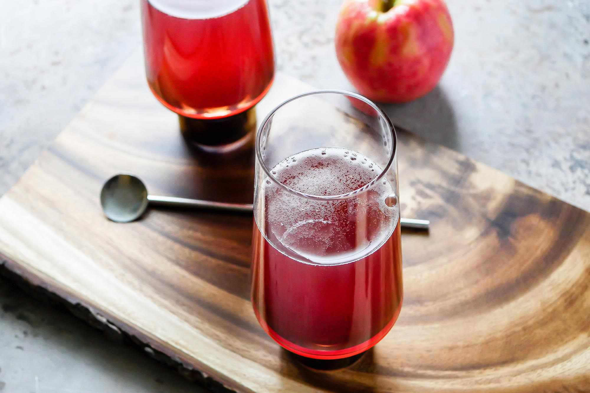 Hard Cider and Pomegranate Mimosa on a wooden board with an apple, stir spoon and second glass behind it.