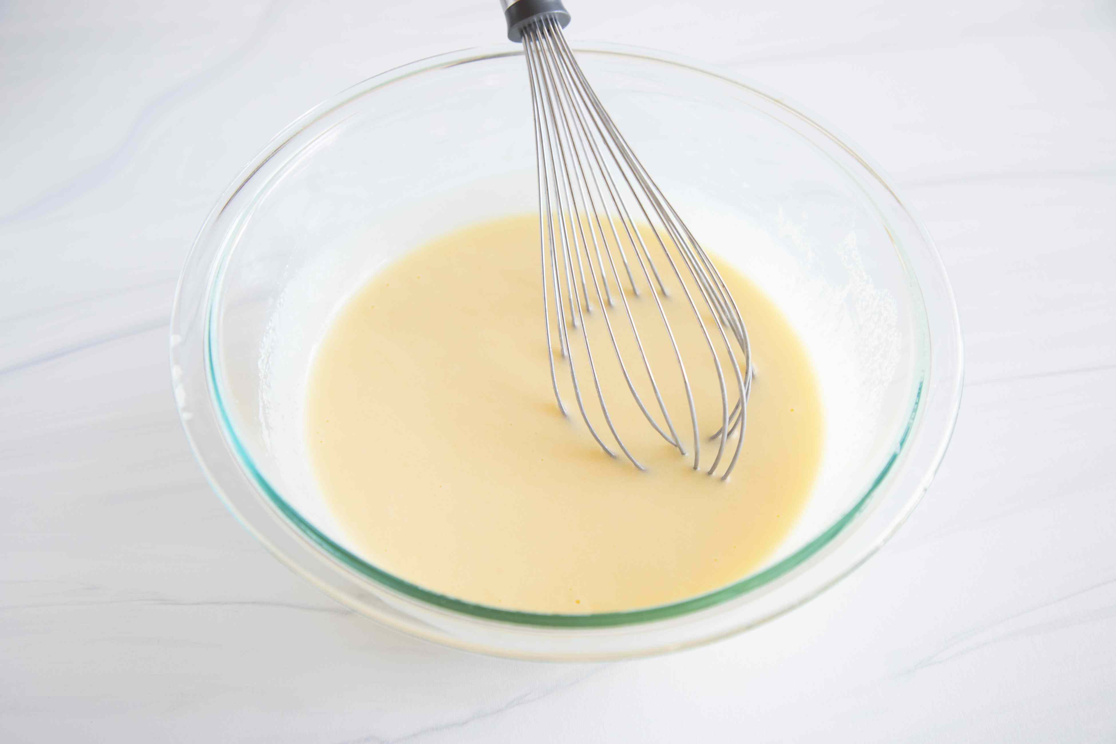 Yogurt Cake Recipe in a glass bowl with a whisk.