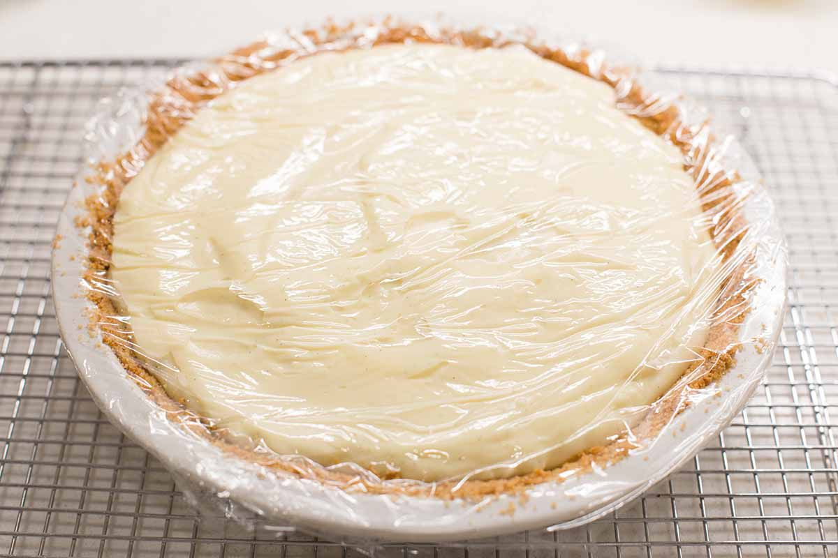 Banana cream pie with clingflim over the top.