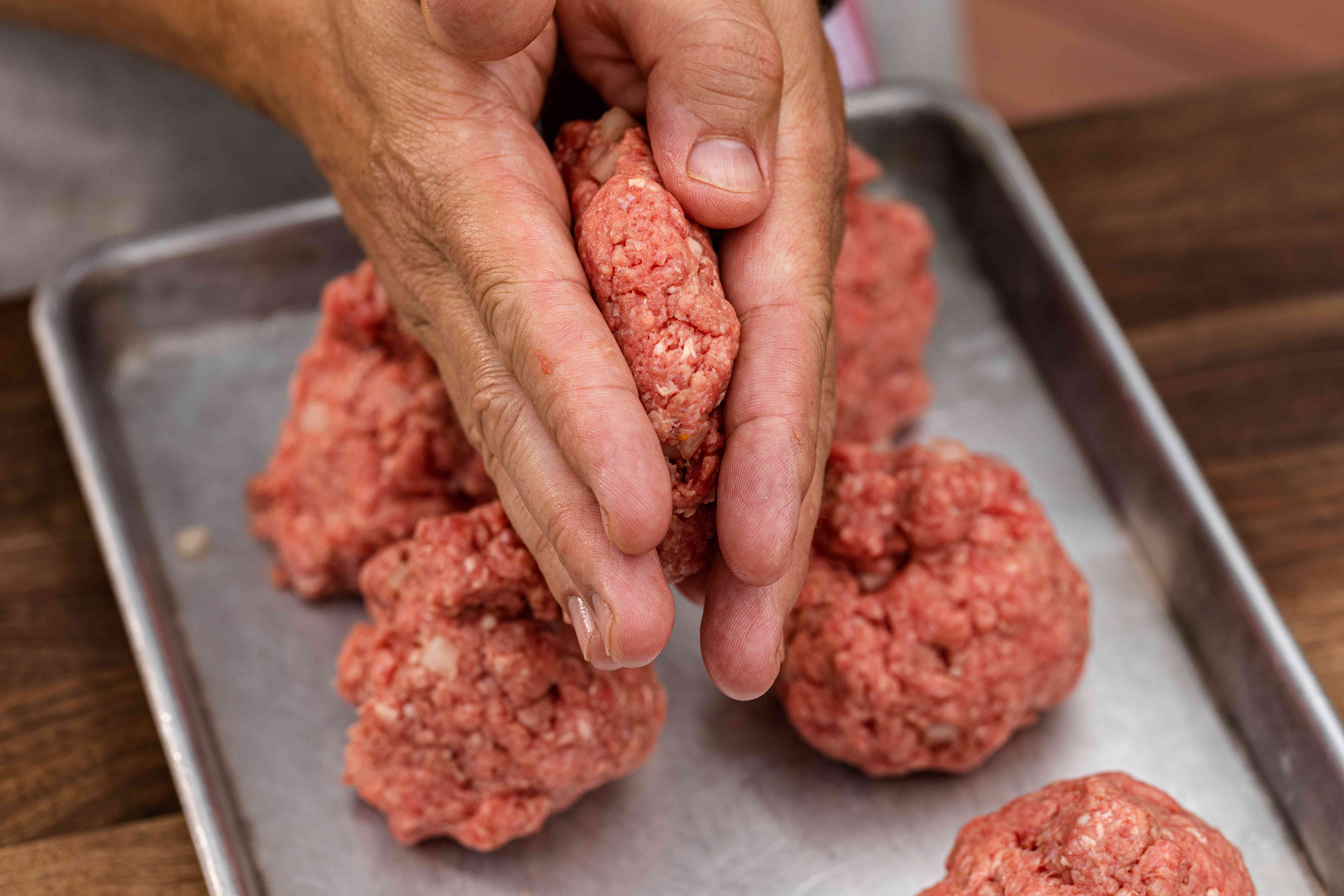 Hands flattening ground beef balls to make a classic bacon cheeseburger