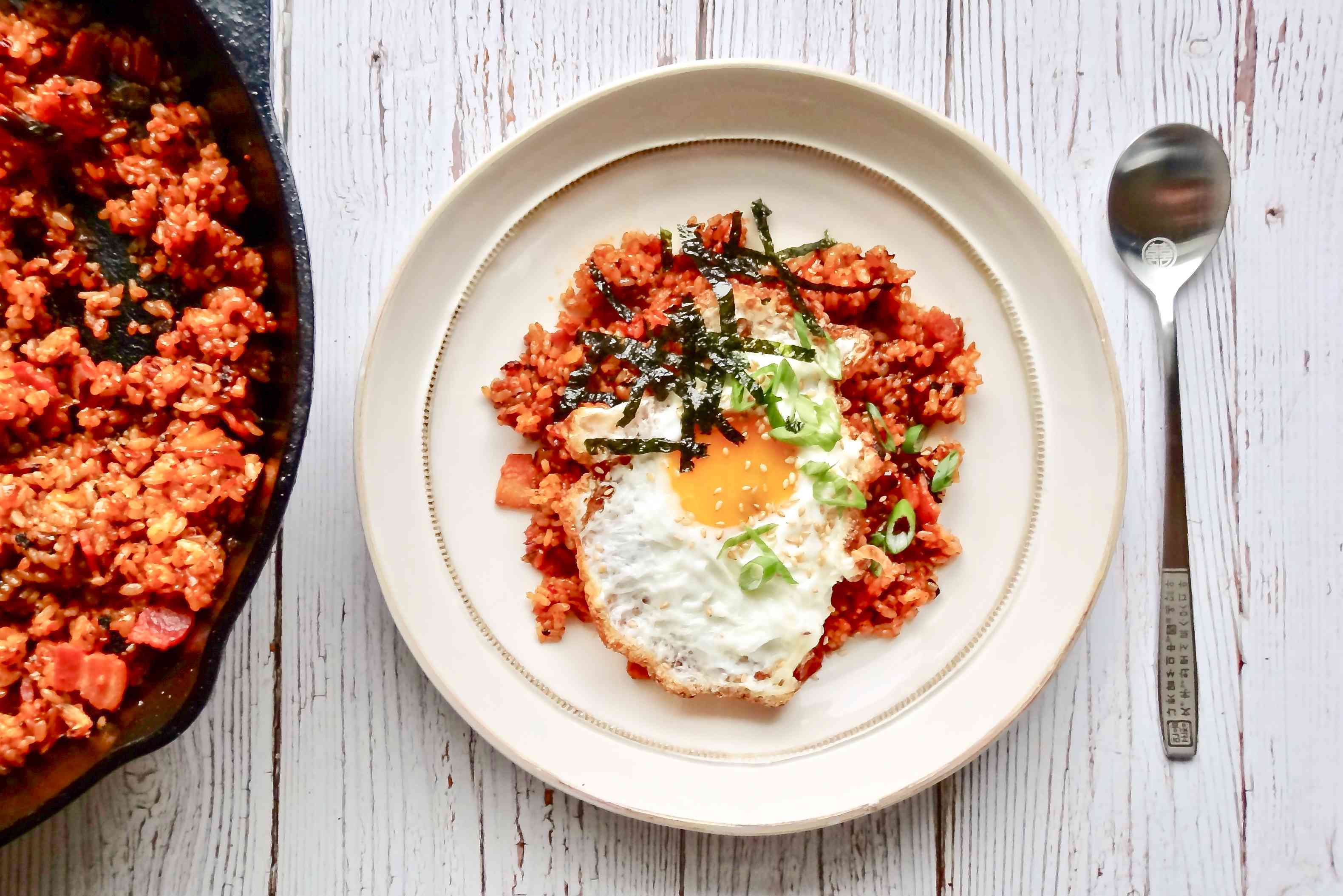 Kimchi fried rice with a fried egg served in a bowl on white wooden background.
