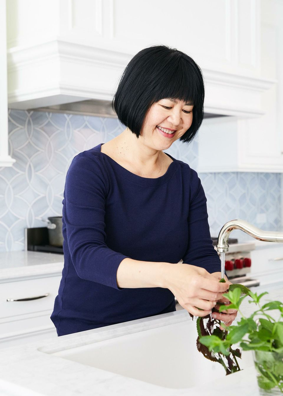 Andrea Nguyen smiling while standing at the kitchen sink rinsing off produce.
