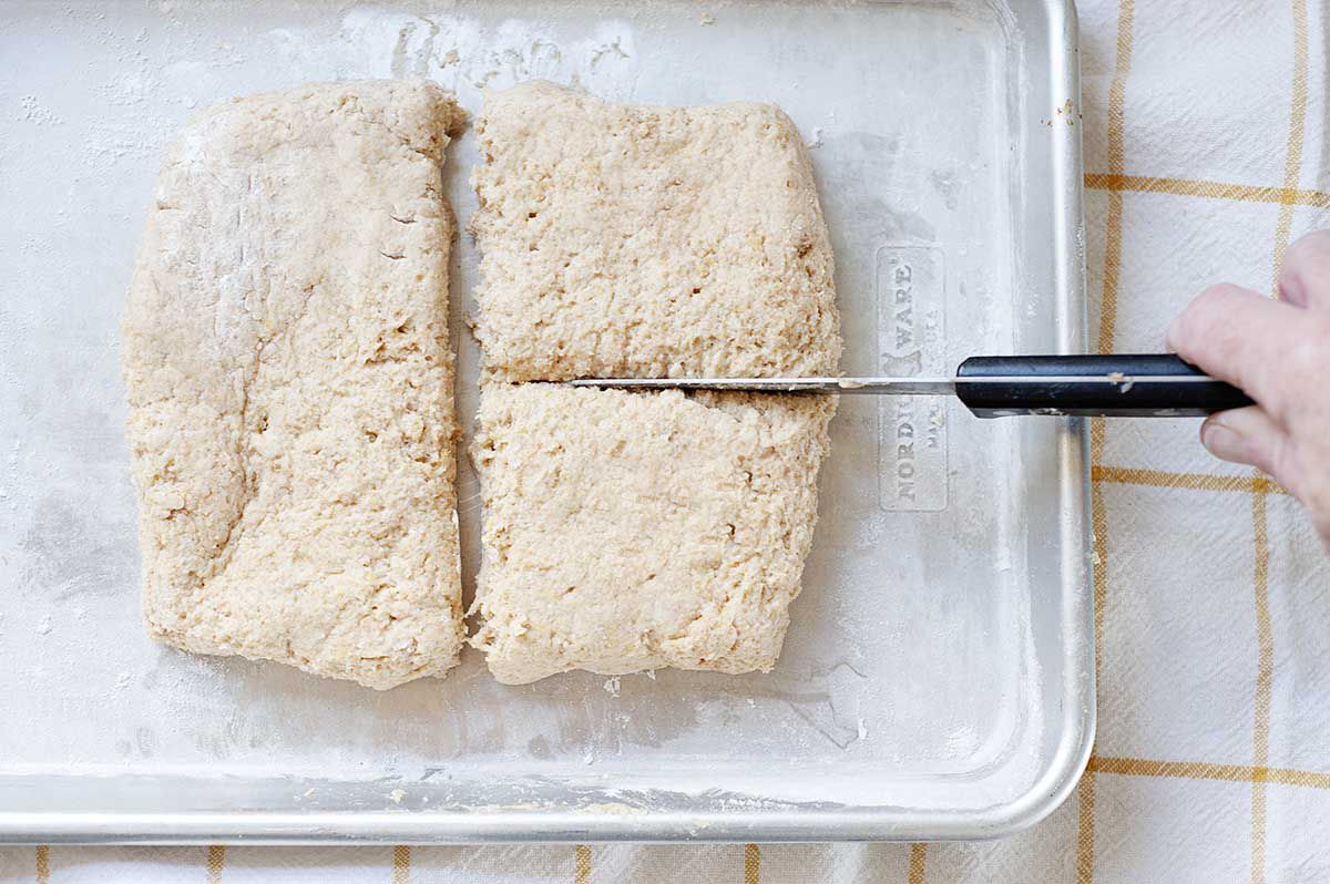 Homemade strawberry shortcake biscuit dough being sliced into four large squares and set on a baking sheet.