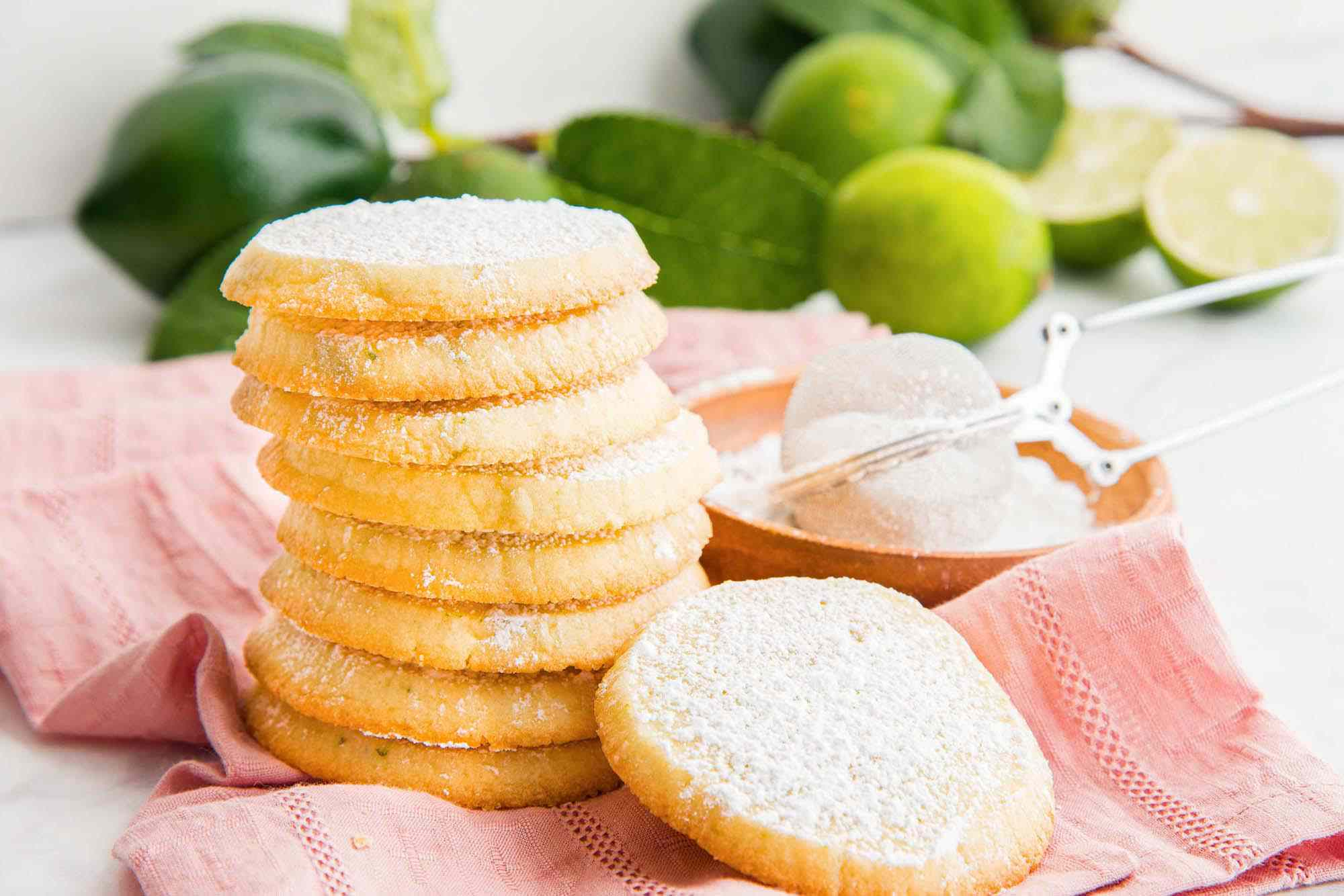 Horizontal view of stacked lime refrigerator cookies coated in powdered sugar and sitting on a pink linen. Limes on their branches are in the background.