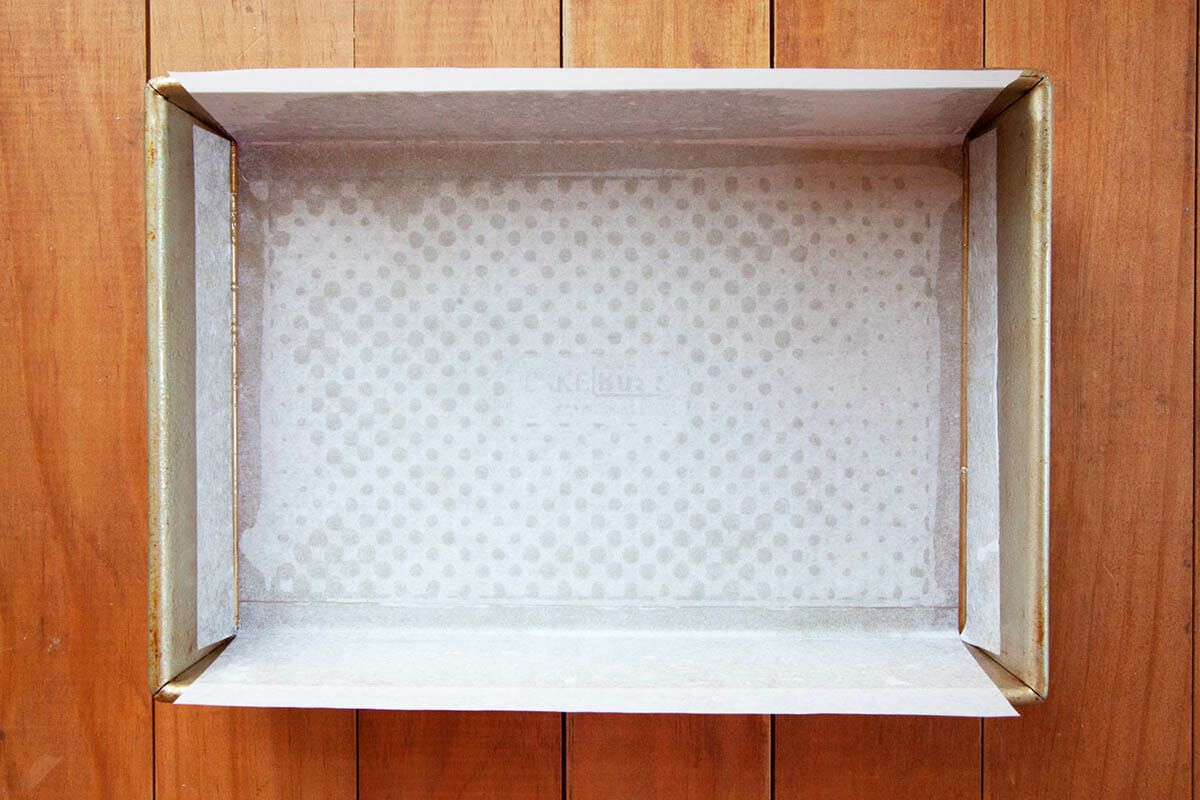 A baking pan lined with parchment paper to show How to Make Gingerbread Bars.