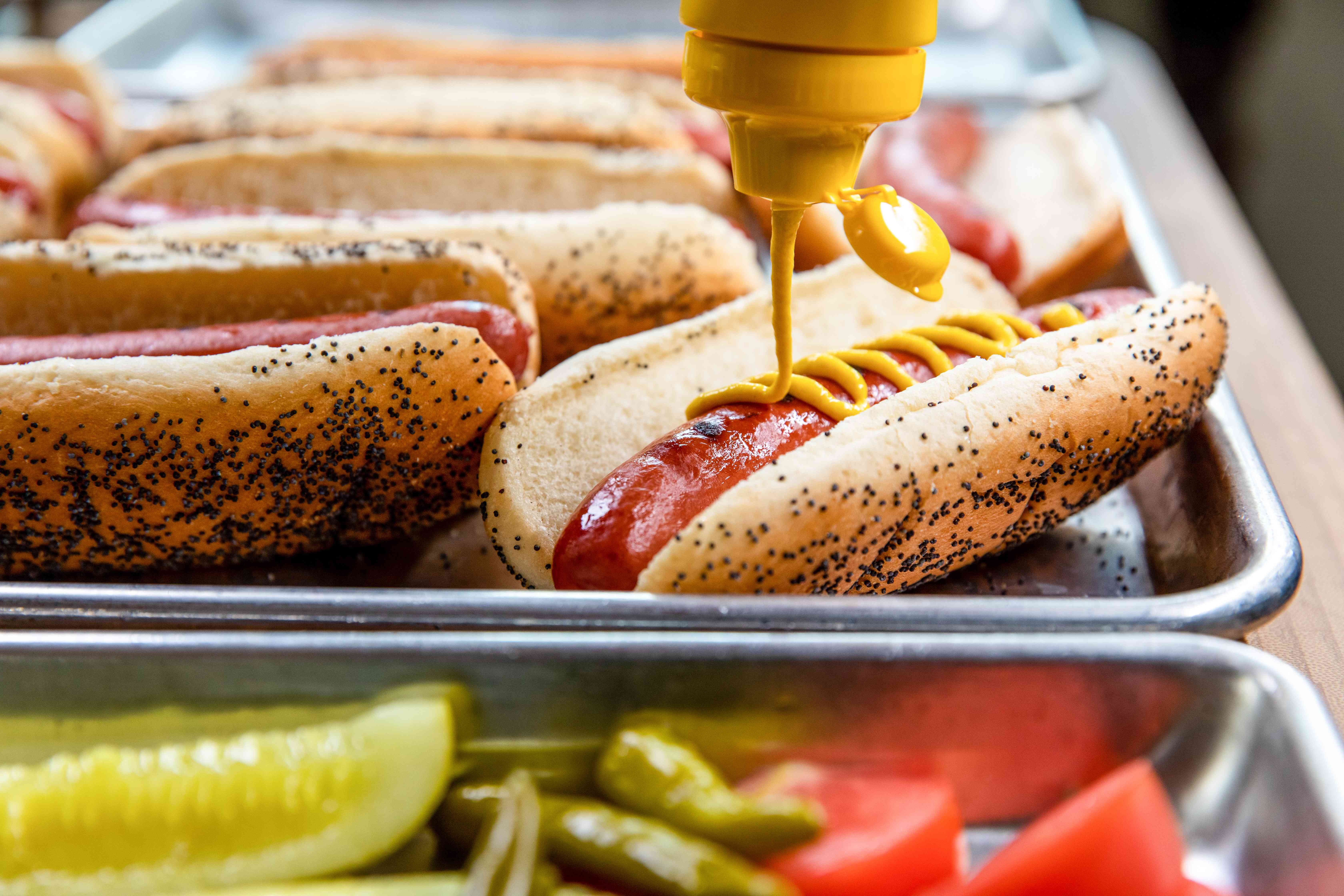 Topping a Chicago hot dog with mustard.