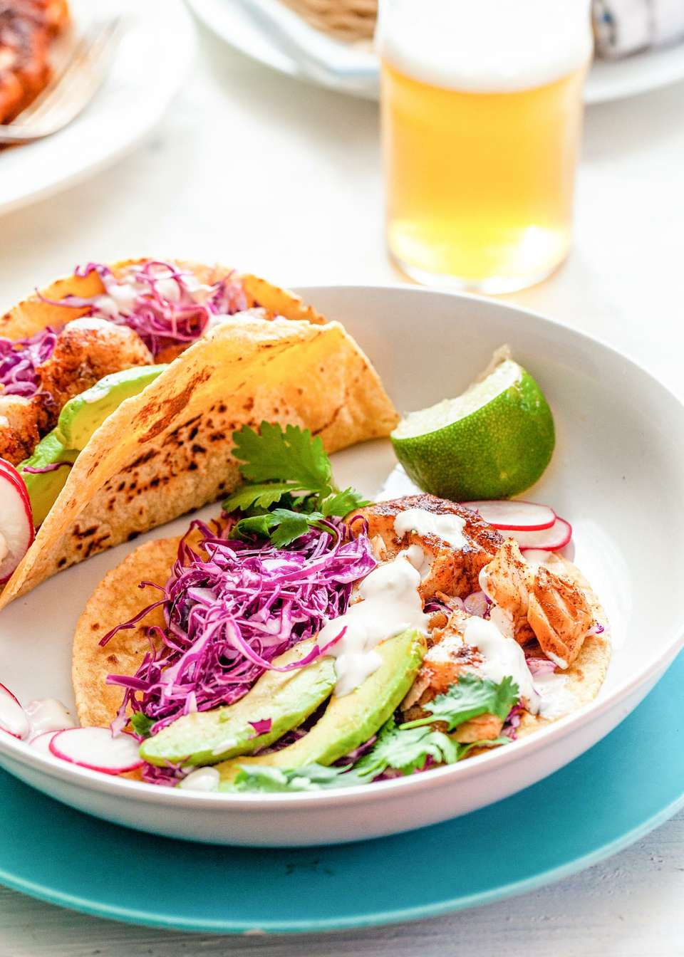 The best fish tacos on a plate. Corn tortillas layered with fish, cabbage, avocado, cilantro and lime.